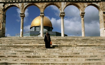 A Palestinian Muslim woman walks by the Dome of the Rock Mosque during the Islamic holy month of Ramadan in Jerusalem's Old City. Oct. 9, 2006