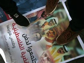 Palestinians step on a placard picturing leaders of Abu Dhabi, Saudi Arabia, Bahrain, Oman, Israel, the U.S. and Jared Kushner, during a protest against the Bahrain conference. Gaza City, June 24, 2019