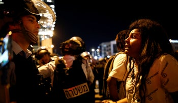 A protester facing off against a policeman in Tel Aviv, July 2, 2019, following the death of 18-year-old Solomon Teka near Haifa on Sunday.