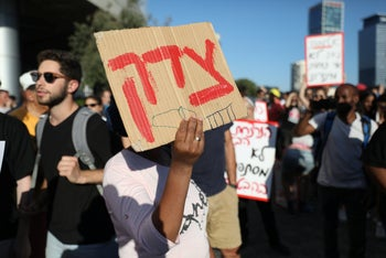 """A demonstrator holds a sign reading """"Justice"""" at a protest over the deadly police shooting of Ethiopian Israeli teen Solomon Teka, in Tel Aviv, July 3, 2019."""