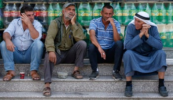 Palestinians sit in front of a shop in the town of Yatta, near Hebron, June 2019.