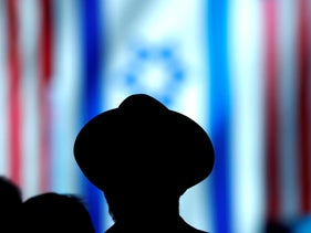 A man silhouetted against Israeli and American flags, Washington, March 25, 2019.