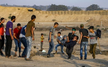 Palestinians rush towards a Palestinian youth carrying away an injured protester during clashes with Israeli forces near the fence along the border, near Bureij in central Gaza, on June 28, 2019.