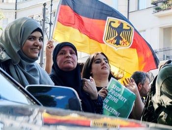 Participants wave a German flag during a demonstration against Israel in Berlin, Germany Saturday June 1, 2019.