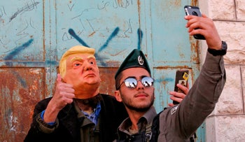 An Israeli soldier takes a selfie with an Israeli settler dressed as U.S. President Donald Trump as during the Jewish Purim holiday. Shuhada Street, divided West Bank town of Hebron. March 01, 2018