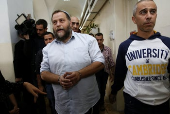 Israeli settler Benzi Gopstein, the leader of the extreme right-wing movement Lehava, is escorted out of a hearing at a Jerusalem court, on December 18, 2014.