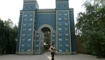 Iraqi armed soldier walks in front of Ishtar Gate of ancient Babylon, Iraq, September 18, 2008.