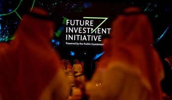 Participants look at a sign of the Future Investment Initiative during the investment conference in Riyadh, Saudi Arabia October 23, 2018