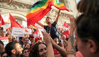 A man carried on shoulders waves the rainbow flag during the celebration of the National Women's Day in avenue Habib Bourguiba in Tunis, on August 13, 2018