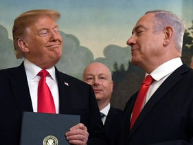 President Donald Trump smiles at Israeli Prime Minister Benjamin Netanyahu, right, after signing a proclamation at the White House in Washington. March 25, 2019