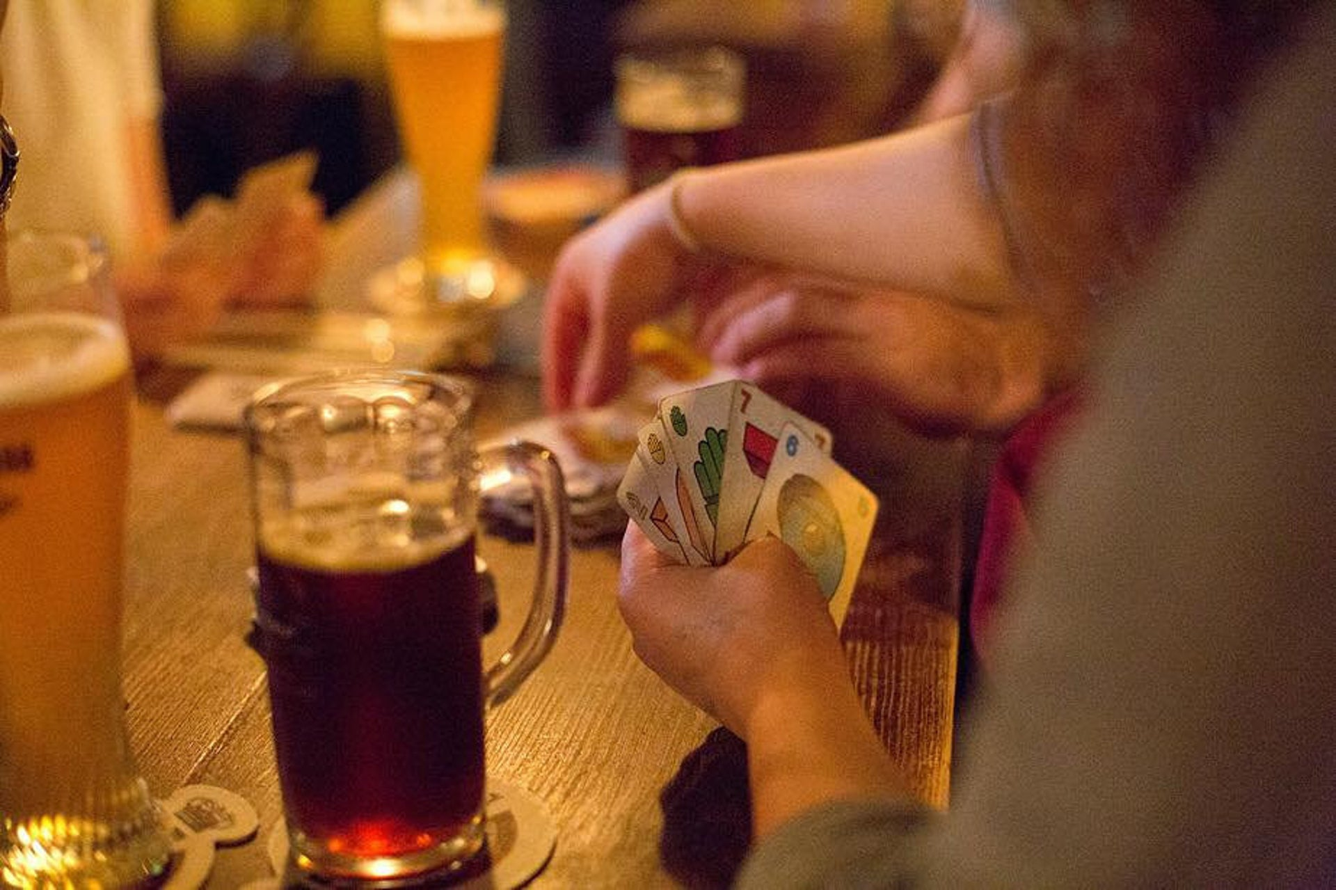 A woman is playing the favorite Israeli card game 'Taki' at the Shuffle bar.