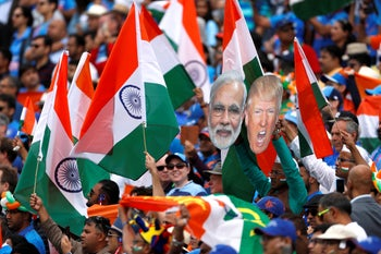 An India cricket team fan holds up masks of a calm Indian Prime Minister Narendra Modi and an agitated U.S. President Donald Trump during the ICC Cricket World Cup at Edgbaston, Birmingham, UK. June 30, 2019