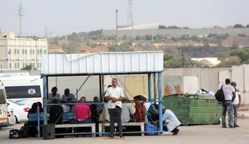 Gazans wait at a bus stop outside the Erez crossing, July 9, 2019.