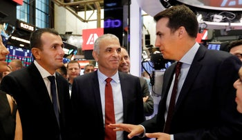 Director General of Israeli Ministry of Finance Shai Babad, left, and Israel's Finance Minister Moshe Kahlon, center, listen to NYSE Vice Chairman John Tuttle during their visit to the New York Stock Exchange trading floor, July 8, 2019.
