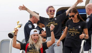 U.S. soccer players Julie Ertz (L), Megan Rapinoe (C) and Alex Morgan celebrate as they exit the plane with the Trophy for the FIFA Women's World Cup while the U.S team arrive at the Newark International Airport, in Newark, New Jersey, U.S., July 08, 2019