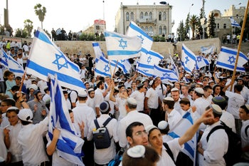"""Jewish youth wave Israeli flags as they participate in a march marking """"Jerusalem Day"""", near Damascus Gate in Jerusalem's Old City June 2, 2019"""