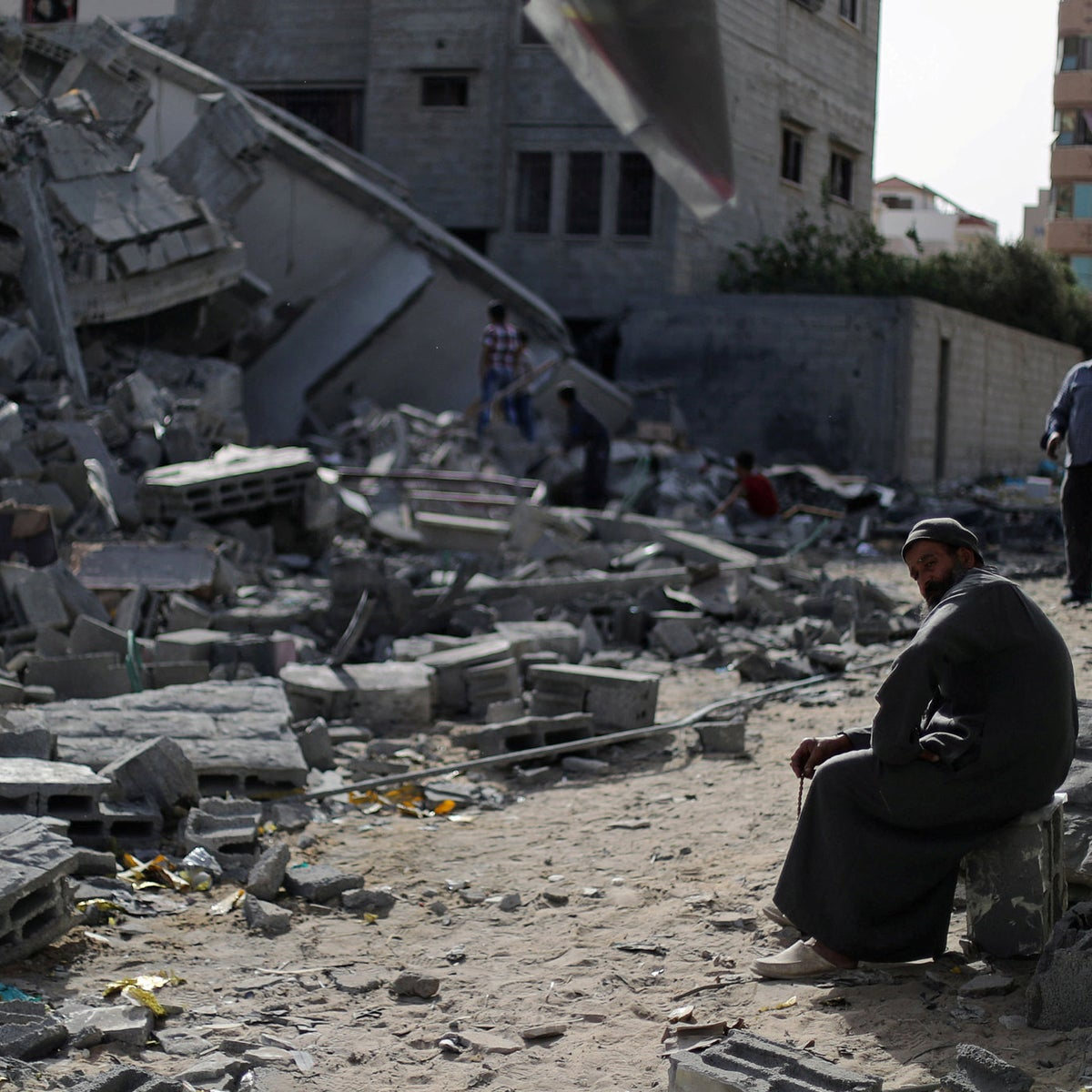 A Palestinian man sits next a building destroyed in an Israeli bombing in Gaza City, May 2019.