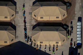 Migrant children are led by staff in single file between tents at a detention facility next to the Mexican border in Tornillo, Texas  June 18, 2018.