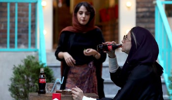 An Iranian drinks a Coca-Cola and smokes a Marlboro cigarette at a cafe in downtown Tehran, Iran, July 10, 2019.