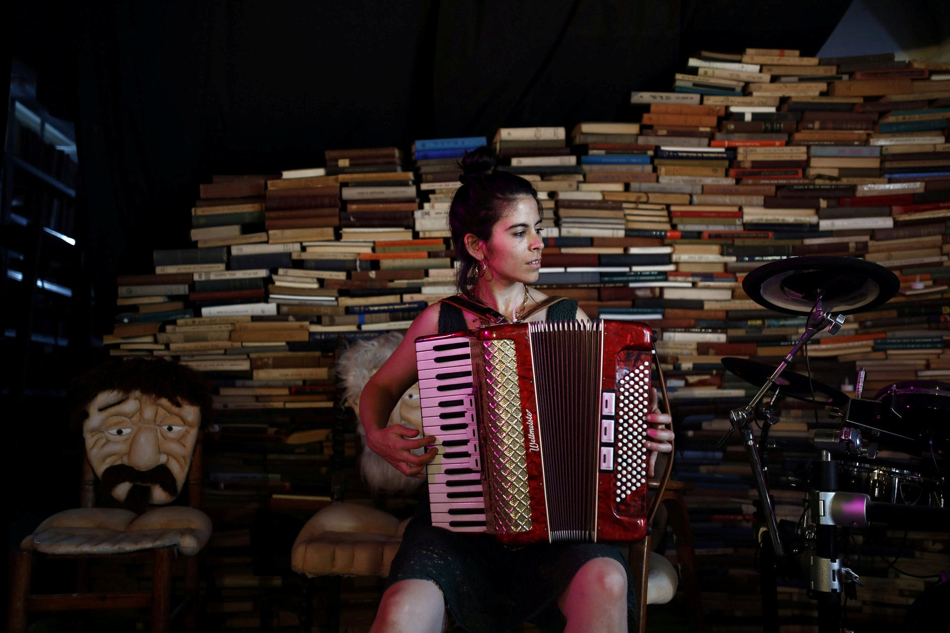 """Lehman plays an accordion next to books placed inside a cultural center used by """"Yung Yidish,"""" a non-profit organisation aiming to preserve Yiddish culture, at the Central Bus Station."""
