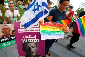 "Members of the LGBT community hold a banner reading in Hebrew ""A homophobic Racist Has to Quit"" during a rally against Israel's Education Minister Rafi Peretz following his remarks on gay conversion therapy, in the Israeli coastal city of Tel Aviv on July 14, 2019"