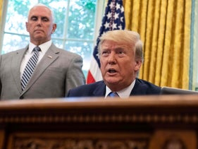 President Donald Trump before signing a bill for border funding legislation as Vice President Mike Pence looks on in the Oval Office at the White House, Washington, DC, July 1, 2019.