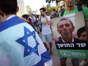 """Protesters hold a sign reading """"Minister of darkness"""" as they call for Israel's Education Minister to resign over comments in support of gay conversion therapy, in Tel Aviv, on Sunday, July 14, 2019."""
