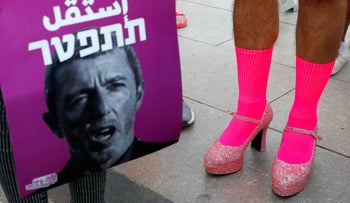 """Members of the LGBT community hold a banner reading in Hebrew """"A homophobic Racist Has to Quit"""" during a rally against Israel's Education Minister Rafi Peretz, July 14, 2019."""