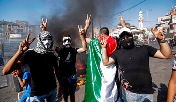 Masked protesters gesturing as they block the main road outside the Palestinian refugee camp of Burj al-Barajneh, south of Beirut, on July 16, 2019.