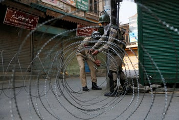 Indian paramilitary soldiers close a road with barbed wire during restrictions in Srinagar, Indian controlled Kashmir. May. 21, 2019