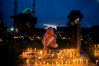 A Kashmiri Shiite Muslim girl light candles on the grave of her relative to mark Shab-e-Barat, on the outskirts of Srinagar, Indian controlled Kashmir. April 20, 2019