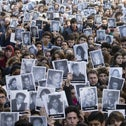 People holding up pictures of the victims of the 1994 bombing of the AMIA Jewish community center in Buenos Aires, Argentina, July 17, 2015.