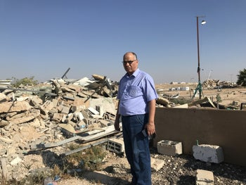 Suleiman al-Atayka standing next to the ruins of his demolished home and aluminum factory in Rahat, southern Israel.