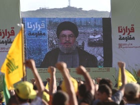 Hezbollah supporters greet Hezbollah leader Hassan Nasrallah, who delivers a speech through a giant TV screen from a secret location, in the Lebanese border village of Aita, on Friday, August 16, 2013.