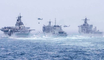 The Amphibious assault ship USS Boxer and amphibious dock landing ship USS Harpers Ferry conducting  a replenishment-at-sea evolution withsupport ship USNS Arctic in the Arabian Sea, July 14, 2019.