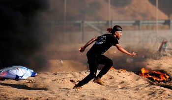 Palestinian protester flees after dropping a flag at burning tires during clashes with Israeli forces along the Gaza border, July 19, 2019.
