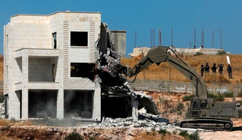 Israeli security forces tearing down one of the Palestinian buildings in the West Bank village of Dar Salah, July 22, 2019
