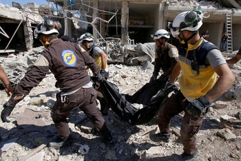 Members of the Syrian civil defence, known as the White Helmets, carry the body of a victim found dead under the rubble following a Russian air strike on Maaret al-Numan in Syria's northwestern Idlib province on July 22, 2019.