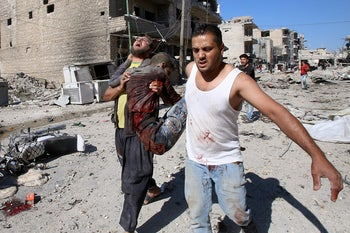 Graphic content / Syrians carry a badly wounded victim amid the rubbble following a Russian air strike on July 22, 2019.