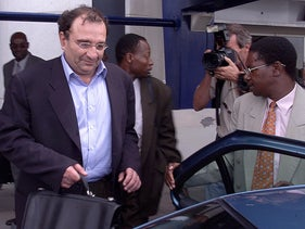 Ari Ben-Menashe being hustled into a car by Zimbabwe security personnel shortly after his arrival at Harare International Airport in 2002.
