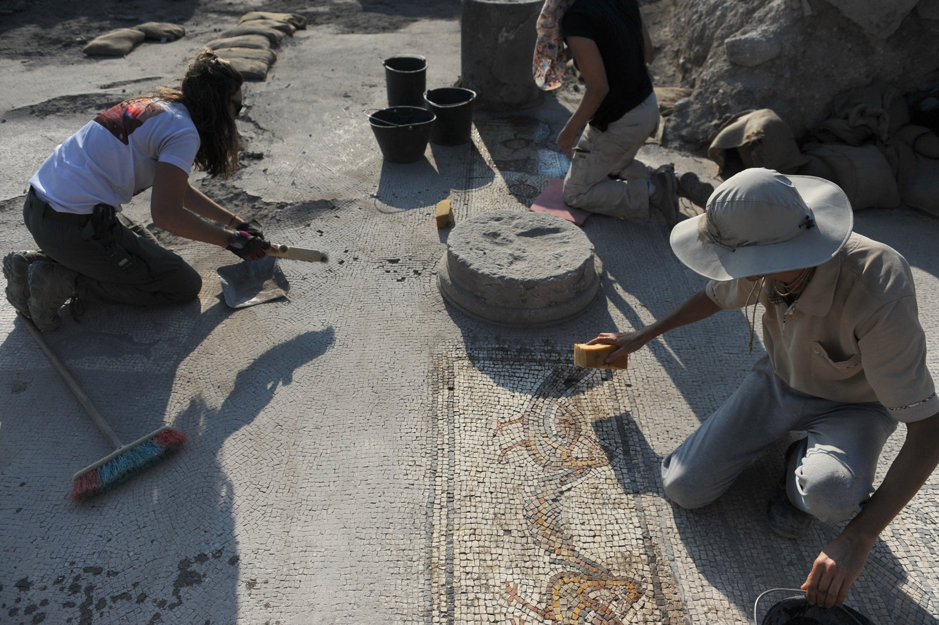Cleaning a mosaic of birds on the floor of the Burnt Church, preserved by the ash of conflagration in Hippos.