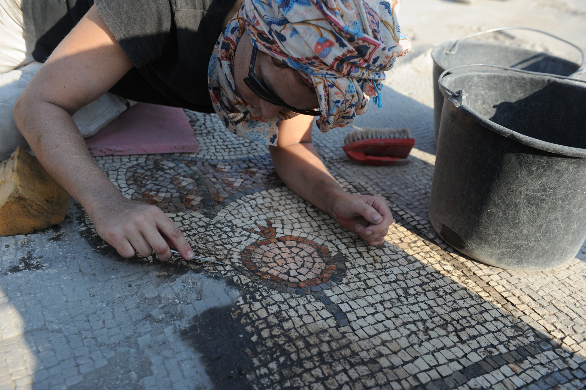 Nina Koskanen, assistant conservator, cleaning the mosaic of a pomegranate, Hippos