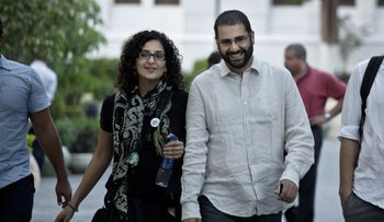 Egypt's leading pro-democracy activist Alaa Abdel-Fattah walks with his sister Mona Seif prior to a conference held at the American University in Cairo, near Tahrir Square, on September 22, 2014.