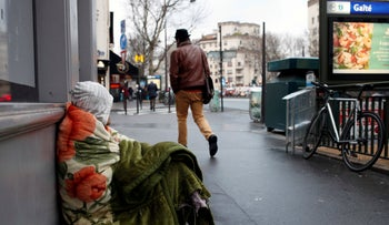 A homeless sits in the streets in Paris, Monday, Feb. 5, 2018.