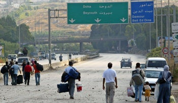 Lebanese civilians cross a bridge linking Beirut to Saida that was attacked by Israeli warplanes in Damour, south Beirut, July 13, 2006.