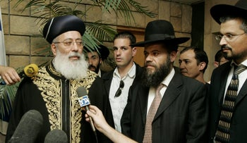 Rabbi Shlomo Amar, left, speaks to the media in his office in Jerusalem Tuesday, May 10, 2005.