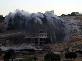 A Palestinian building is blown up by Israeli forces in the village of Sur Baher, East Jerusalem, July 22, 2019.