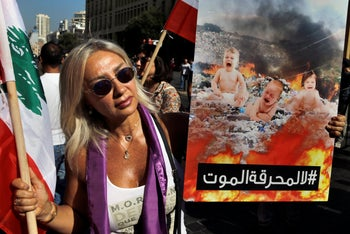 """A protester holds a poster with Arabic that reads:"""" No to the death incinerators,"""" during a demonstration in front of the municipality building of Beirut, Lebanon, July 4, 2019."""