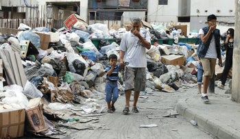 Residents cover their noses as they walk past garbage piled up along a street in Beirut, Lebanon, August 26, 2015.