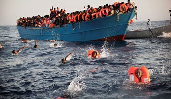 Migrants jump into the water from a wooden boat as they are helped by members of an NGO during a rescue operation at the Mediterranean Sea, off Libya, August 29, 2016.